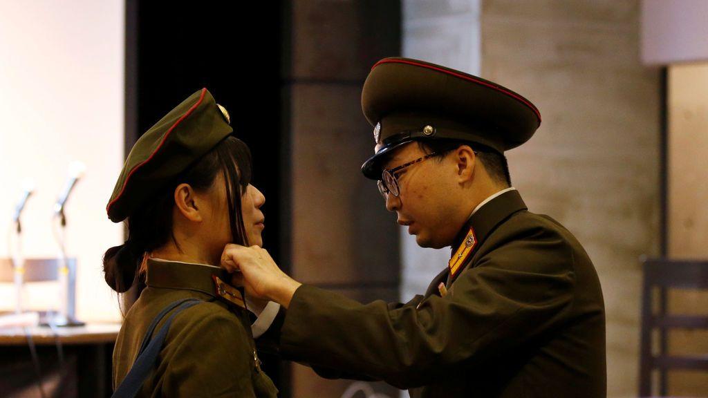 Los fanáticos de Corea del Norte vestidos como el Ejército Popular de Corea ajustan su ropa frente a un retrato del fallecido líder norcoreano Kim Jong Il antes de un evento de fanáticos de Corea del Norte en Tokio, Japón