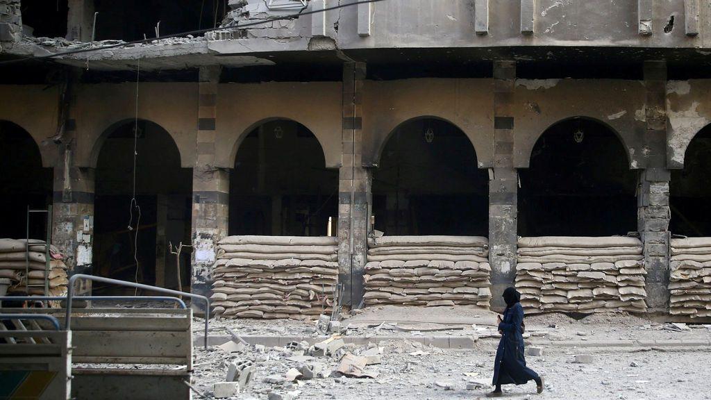 Una mujer pasea junto a un edificio dañado después de un bombardeo en Douma