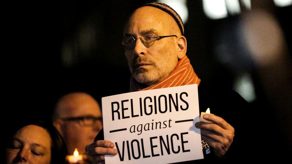 Un hombre sostiene un letrero durante una vigilia con velas para las víctimas del ataque de camioneta pickup en Foley Square en la ciudad de Nueva York, EE. UU