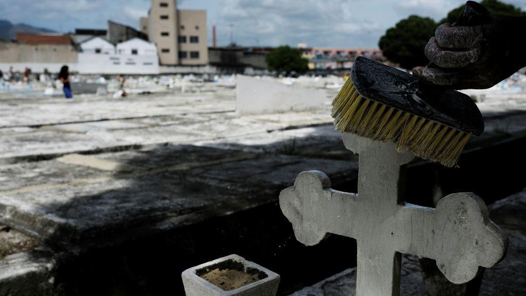 Un joven pinta una tumba con lima durante el Día de Muertos en Brasil