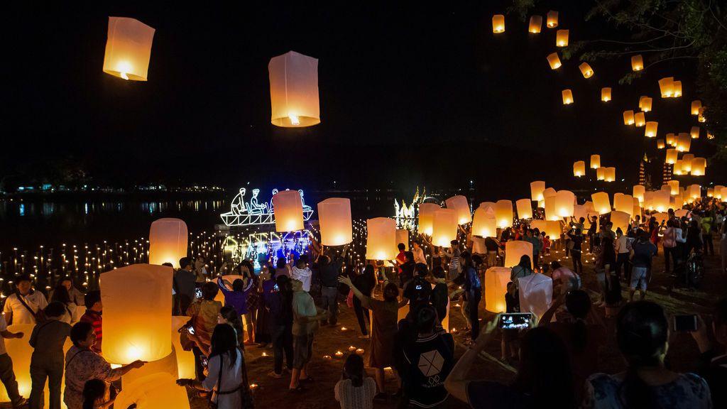 Un grupo de personas lanza linternas flotantes durante el Festival de Yee Peng