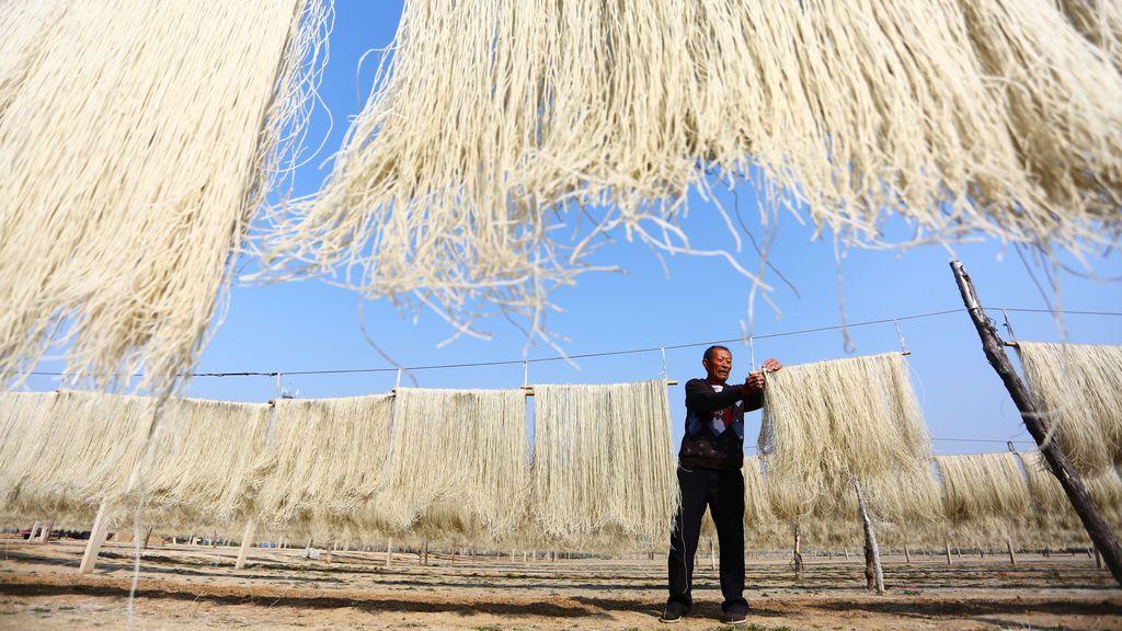 Un hombre cuelga hebras de fideos de batata para secar en Zaozhuang, provincia de Shandong, China, el 2 de noviembre de 2017