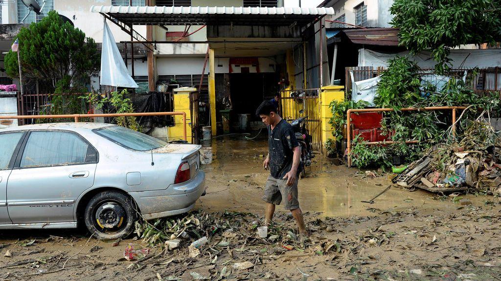 Un hombre camina por un camino embarrado después de una inundación en George Town, Penang, Malasia