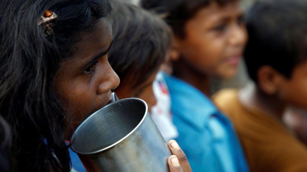 Una niña refugiada Rohingya sostiene una taza mientras espera en una cola fuera del centro de distribución en el campo de refugiados de Kutupalong, cerca de Cox's Bazar