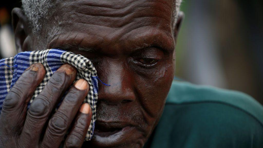 Un refugiado sudanés se seca las lágrimas tras enterarse de la muerte de su hijo