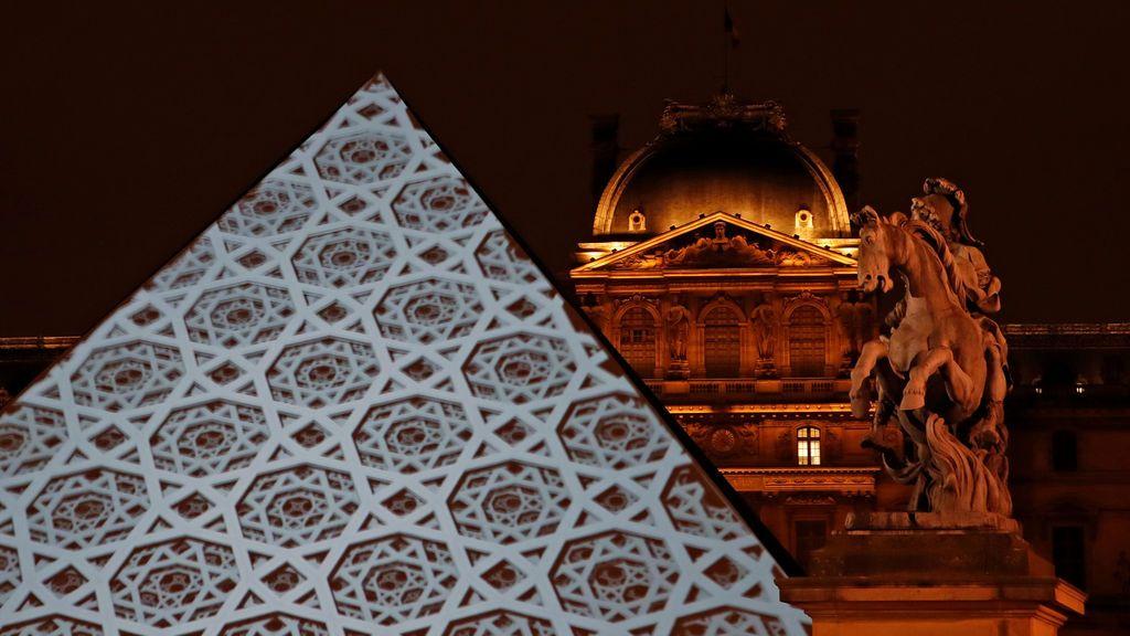 La imagen de la cúpula del nuevo museo del Louvre de Abu Dhabi se proyecta en la pirámide del conocido museo parisino