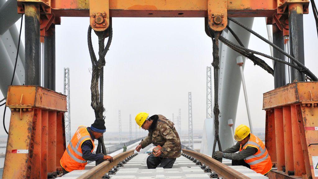 Los trabajadores refuerzan las vías para construir una nueva línea ferroviaria que conecta Tangshan y Caofeidian en una estación de ferrocarril en Tangshan, provincia de Hebei, China