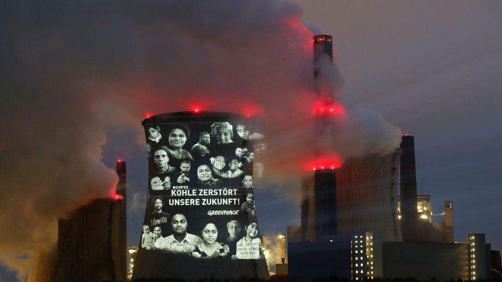 """Activistas de la organización ambientalista Greenpeace proyectan un lema que dice: """"No hay futuro en combustibles fósiles"""" en la torre de enfriamiento de la planta de carbón de RWE, una de las mayores compañías eléctricas de Europa en Neurath, noroeste de Colonia, Alemania"""