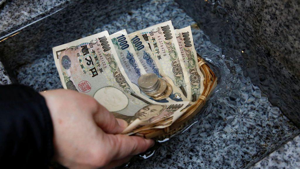 Un visitante lava monedas y monedas de yenes japoneses en agua para rezar por la prosperidad en el santuario de Koami en el distrito comercial Nihonbashi de Tokio