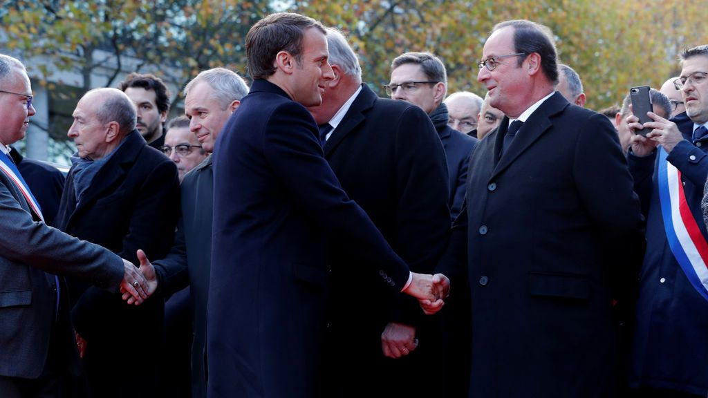 El presidente francés Emmanuel Macron (L) estrecha la mano del ex presidente francés Francois Hollande frente a una placa conmemorativa frente al estadio Stade de France, en Saint-Denis, cerca de París, Francia
