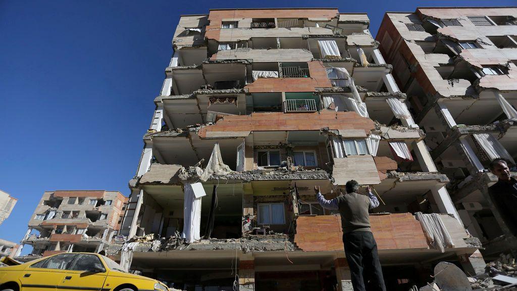 Un hombre reacciona mientras observa un edificio dañado en el condado de Sarpol-e Zahab en Kermanshah, Irán
