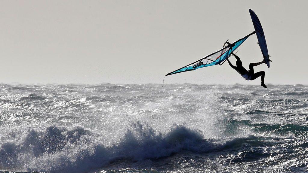 Un surfista sale del agua cuando fuertes vientos azotan el muelle de Marsella, Francia