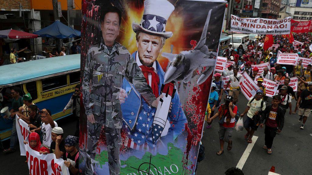 Los manifestantes portan retratos del estadounidense Donald Trump y del presidente filipino Rodrigo Duterte durante una manifestación contra la visita del presidente estadounidense Donald Trump a Manila, Filipinas
