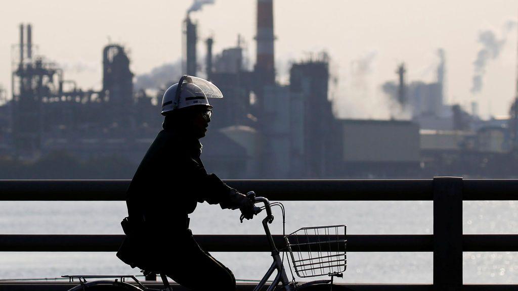 Un trabajador realiza un ciclo cerca de una fábrica en la zona industrial de Keihin en Kawasaki, Japón