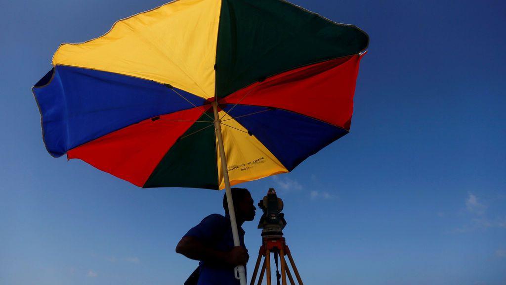 Un topógrafo toma mediciones, en un nuevo proyecto de vía férrea, en la playa de Colombo, Sri Lanka