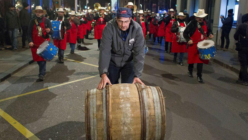Los músicos se presentan mientras que un hombre rueda un barril de vino de Beaujolais Nouveau para el lanzamiento oficial de la añada 2017 en el centro de Lyon, Francia