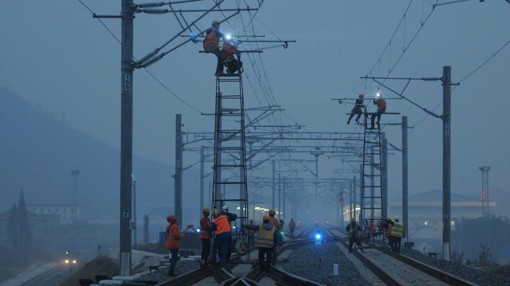 Los trabajadores controlan las líneas eléctricas aéreas en la estación de Duchang, como parte de la línea ferroviaria Jiujiang-Jingdezhen-Quzhou en Jiujiang, China