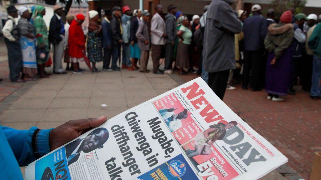 Un hombre lee un periódico mientras los residentes hacen fila para sacar dinero de un banco en Harare, Zimbabwe