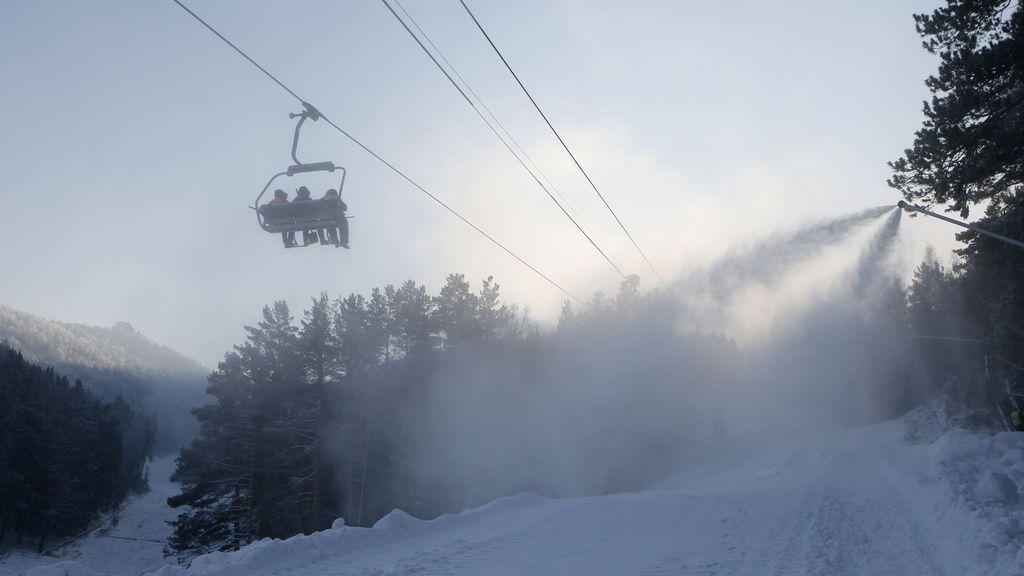 Los empleados usan un telesilla mientras una máquina de nieve rocía nieve artificial durante la preparación de las pistas para la temporada de esquí en la estación de esquí Fun Park Bobrovy Log, con la temperatura del aire a menos 16 grados Celsius