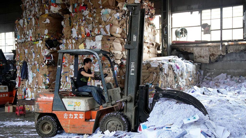 Un trabajador trabaja en una estación de reciclaje de productos de papel en Shanghai, China