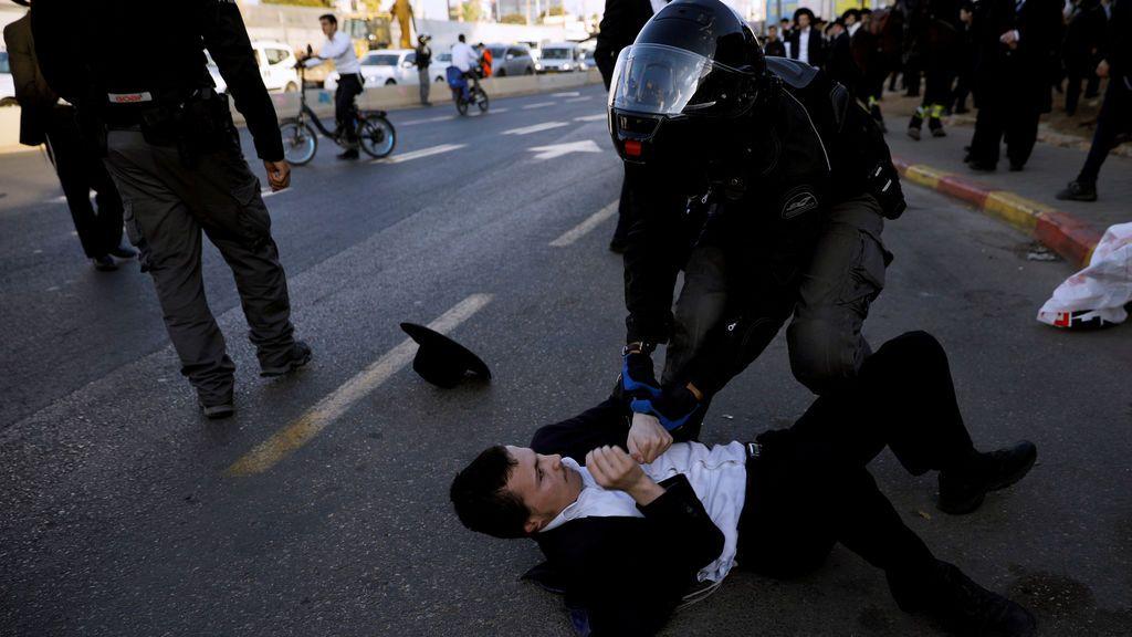 Un agente de la policía israelí forcejea con un judío ultraortodoxo durante una manifestación contra la detención de miembros de su comunidad