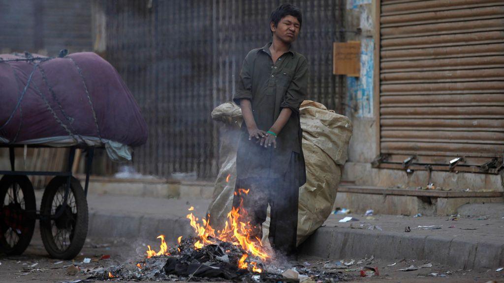 Un niño que recoge papeles usados para reciclar se calienta cerca de un incendio en una calle a primera hora de la mañana en Karachi, Pakistán