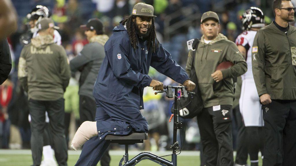El esquinero de los Seahawks de Seattle, Richard Sherman, observa cómo los compañeros de equipo se calientan antes de un juego contra los Atlanta Falcons en CenturyLink Field