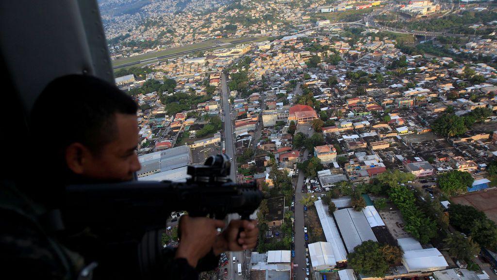 """Un soldado, a bordo de un helicóptero militar, coge su arma durante una patrulla dentro de la operación """"Paz y Democracia II"""""""