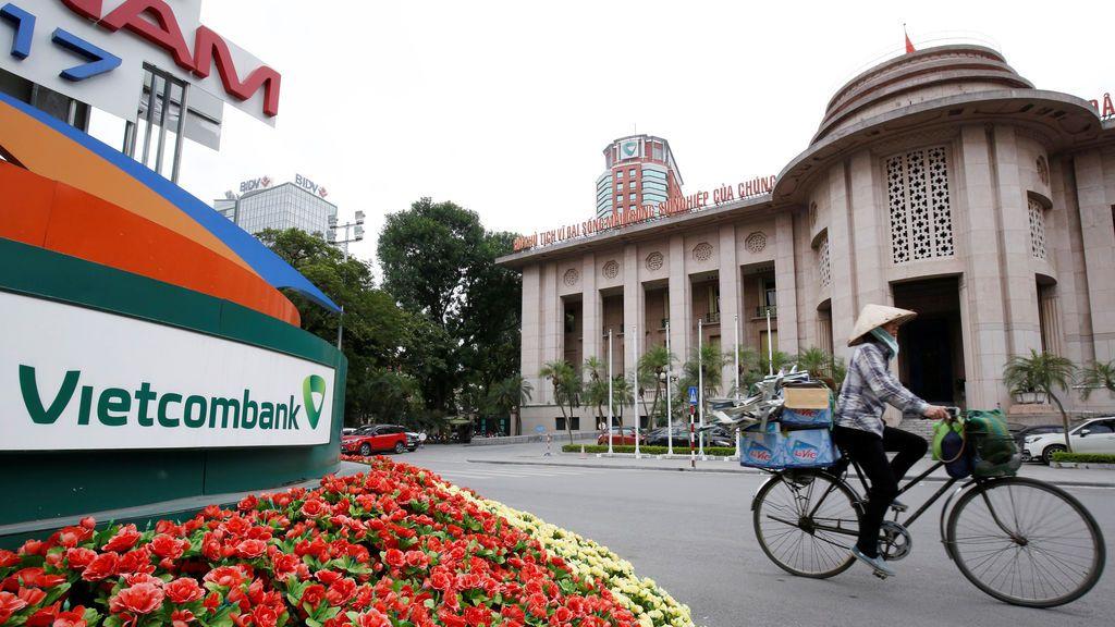 Una mujer monta una bicicleta pasando el logotipo de Vietcombank, frente al edificio del Banco del Estado, cerca de las oficinas de Vietcombank y del Banco de Inversión y Desarrollo de Vietnam en el centro de Hanói, Vietnam