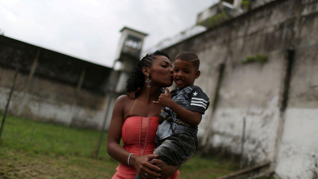 Una presa, participante de un conocido concurso de belleza, coge a su hijo en brazos en Brasil