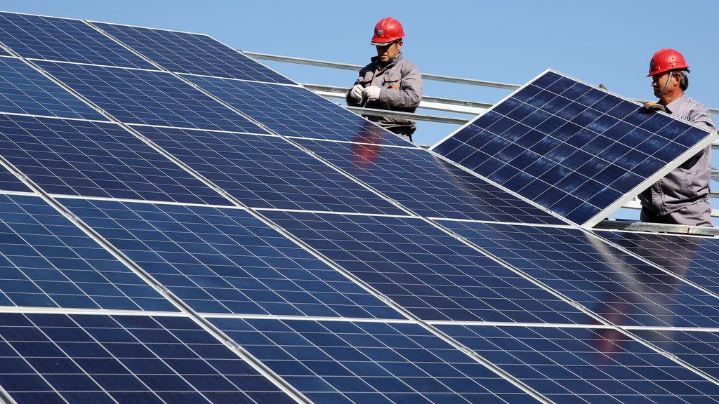 Los trabajadores instalan paneles solares en una casa residencial en una aldea en Dongying, provincia de Shandong, China