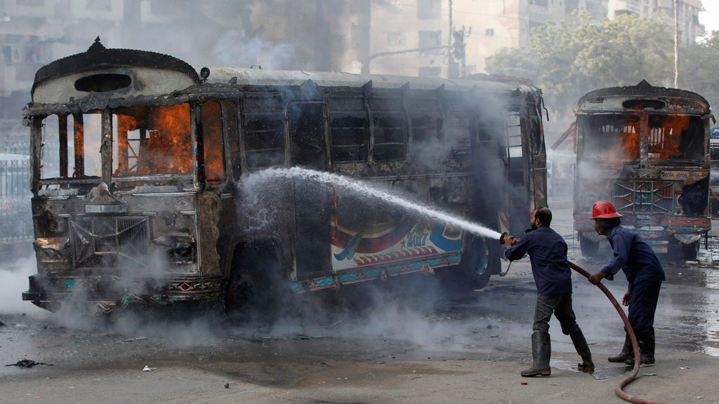 Los bomberos disparan un incendio en los autobuses, que según los medios locales fueron incendiados por personas después de que una niña fue asesinada por exceso de velocidad, a lo largo de una carretera en Karachi, Pakistán