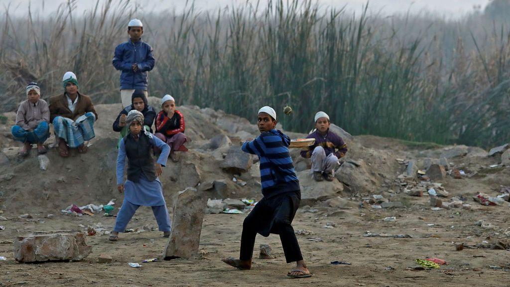 Los niños juegan al cricket en las orillas del río Yamuna en Delhi, India