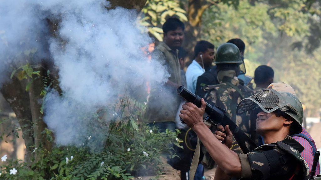 Un policía disparó un proyectil de gas lacrimógeno para dispersar a los residentes, mientras la policía llega a demoler chozas que los funcionarios forestales afirmaron fueron construidas ilegalmente en el Santuario de Vida Silvestre Amchang, en Guwahati, India