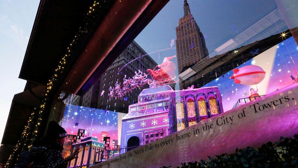 La gente mira las decoraciones navideñas en la sede de macy's mientras se ve el Empire State Building en la imagen reflejada en la ciudad de Nueva York, Nueva York, EE. UU
