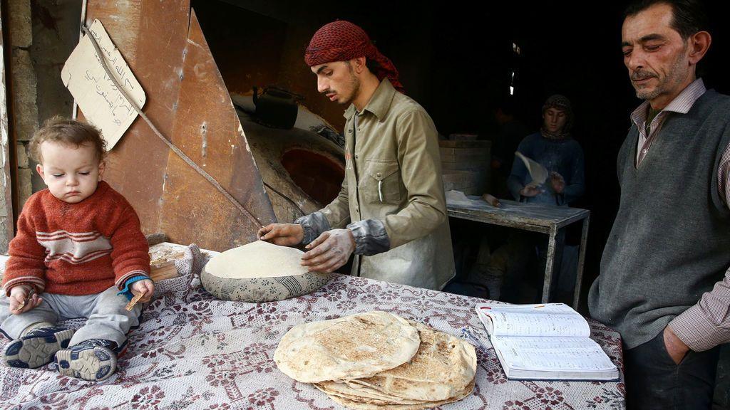 Un hombre hace pan en la ciudad de Hamoria, al este de Ghouta, en Damasco, Siria