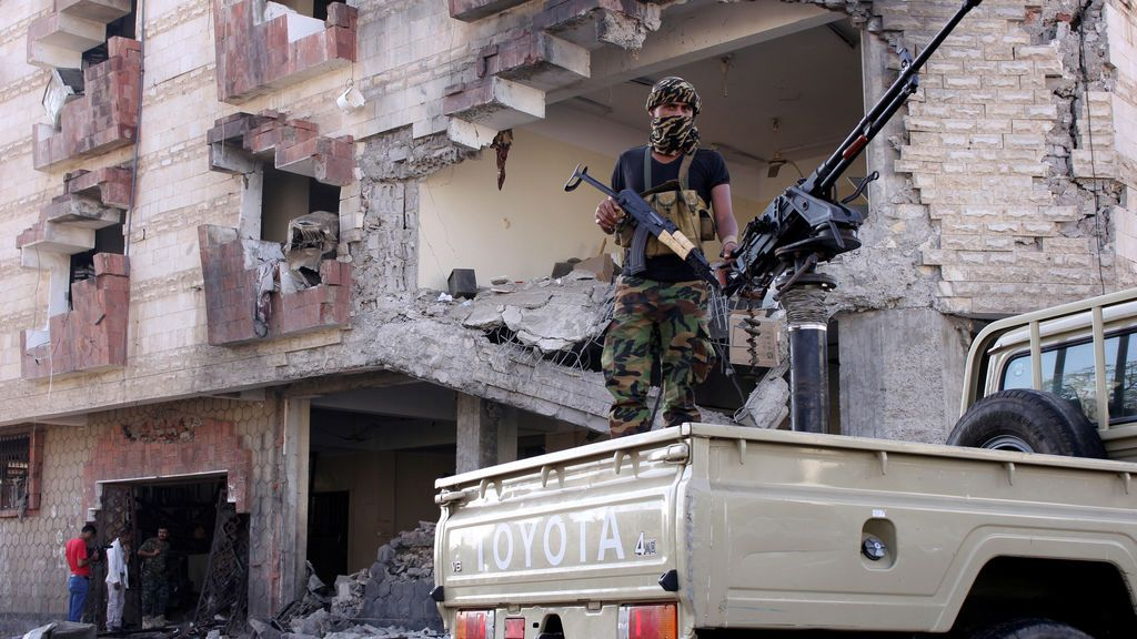 Un soldado de policía arma una ametralladora montada en una patrullera en el lugar de un ataque con coche bomba afuera de las oficinas del Ministerio de Finanzas en la ciudad portuaria de Aden, Yemen