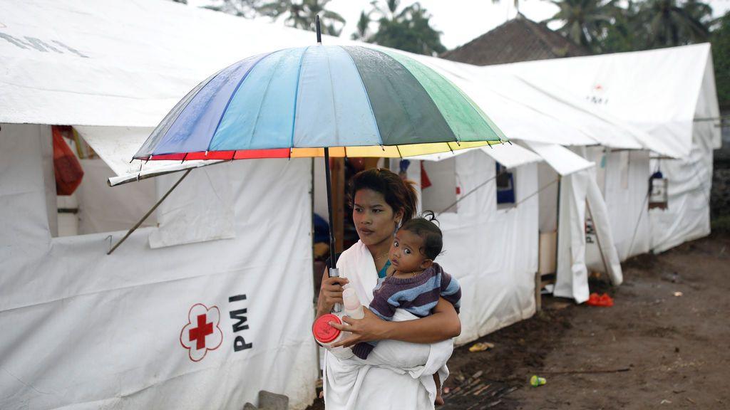 Una mujer lleva a un bebé en un campamento para personas que han sido evacuadas de aldeas cercanas al volcán Monte Agung en Rendang, Karangasem, Bali, Indonesia