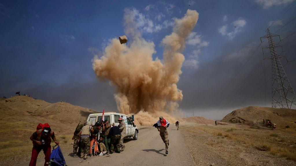 Fuerzas de movilización populares chiítas (PMF) huyen y se protegen de una bomba en las afueras de Hawija, Irak