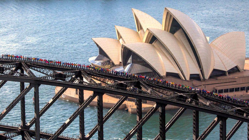 Una foto suministrada muestra la Casa de la Ópera de Sydney detrás de algunos de los 360 estudiantes universitarios de Canadá y China que se encuentran sobre el Puente del Puerto de Sydney para establecer un nuevo récord para la mayor cantidad de personas paradas en el arco del puente en Sydney , Australia