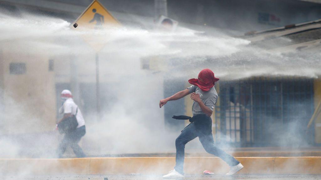 Partidarios de Salvador Nasralla combaten con la policía mientras esperan los resultados de las elecciones en Tegucigalpa, Honduras