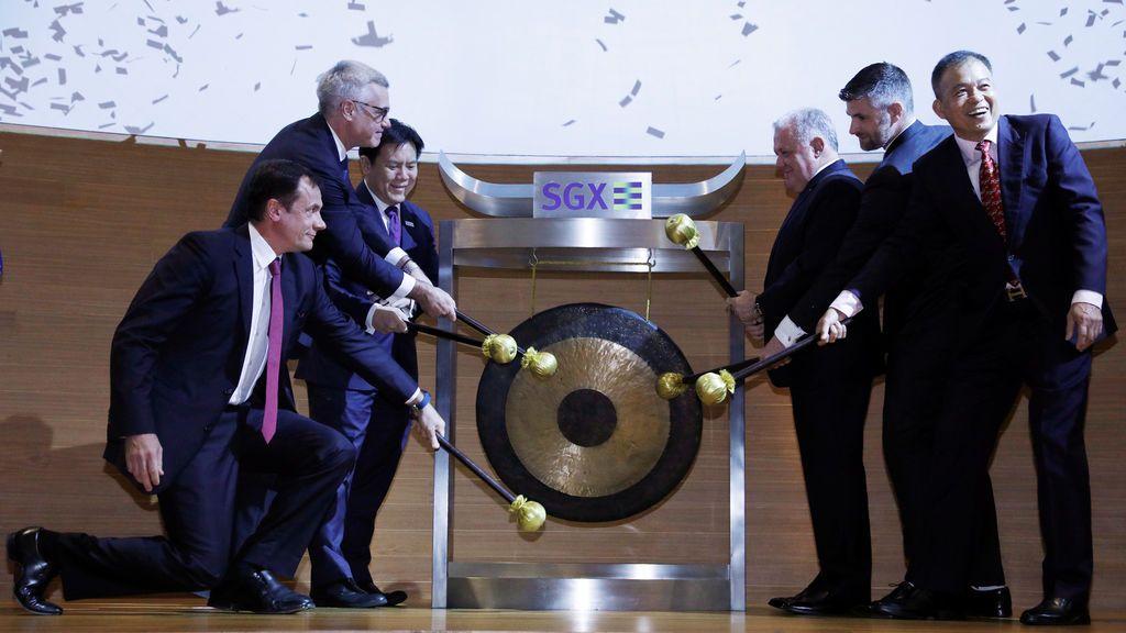 El CEO de Cromwell Property Group, Paul Weightman (3ª R) suena el gong durante una ceremonia de cotización de los REIT Europeos de Cromwell en el Singapore Exchange (SGX) en Singapur