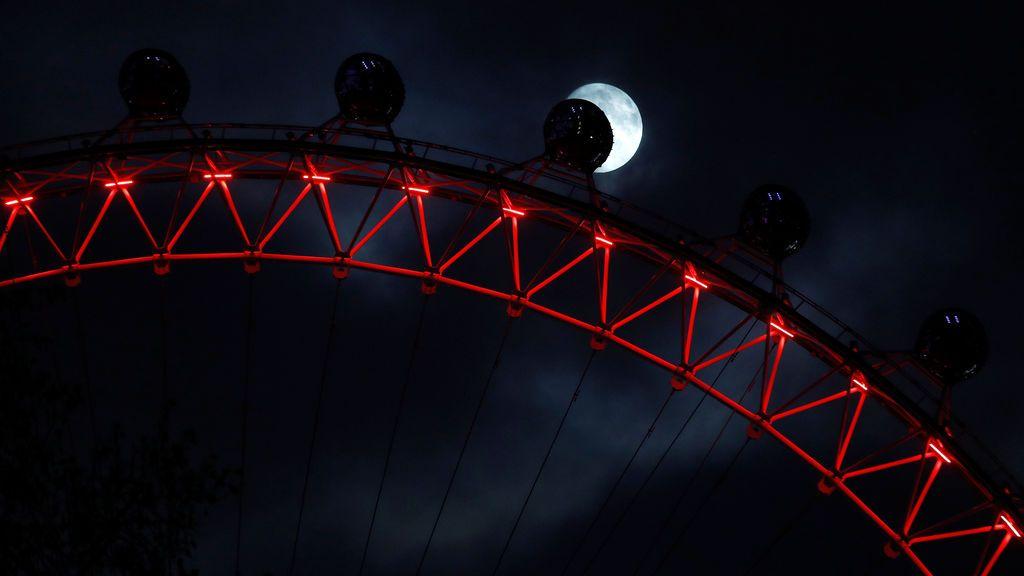 La luna se alza detrás de una cápsula en el London Eye, iluminada de rojo por el Día Mundial del SIDA