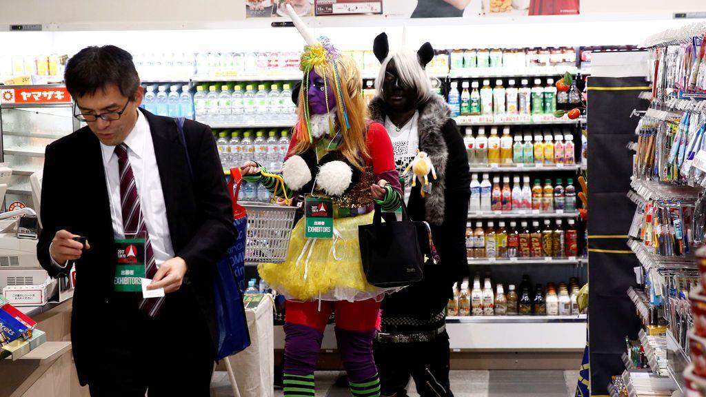 Mujeres vestidas con trajes compran productos en una tienda de conveniencia en el Tokyo Comic Con en Makuhari Messe en Chiba, Japón