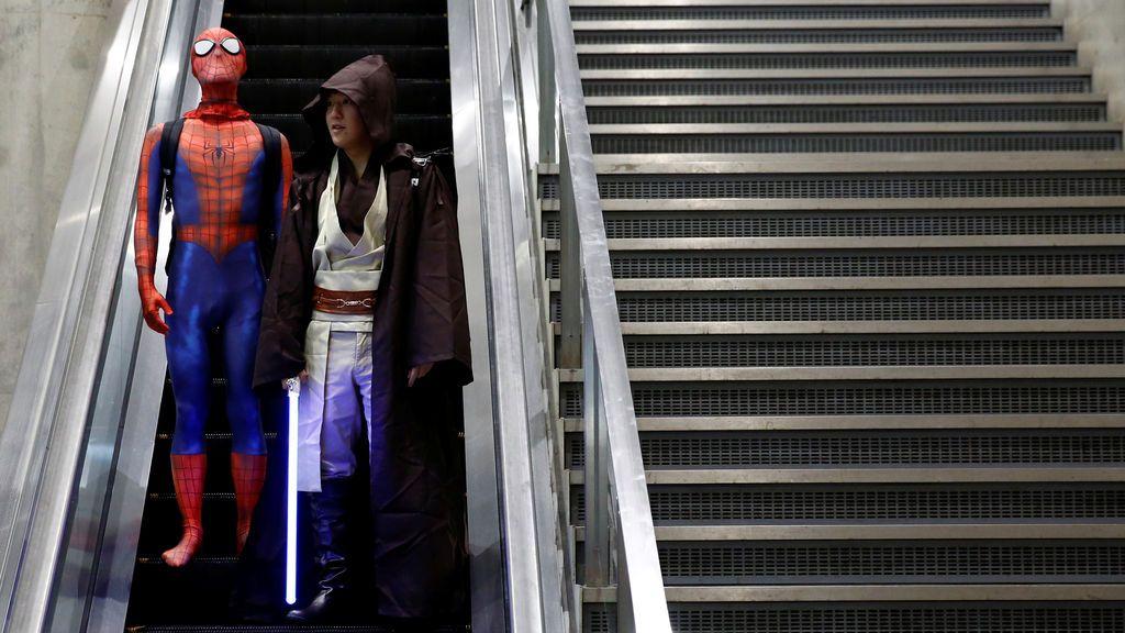 Los visitantes en trajes de Spider-Man y Star Wars montan una escalera mecánica en el Tokyo Comic Con en Makuhari Messe en Chiba, Japón,