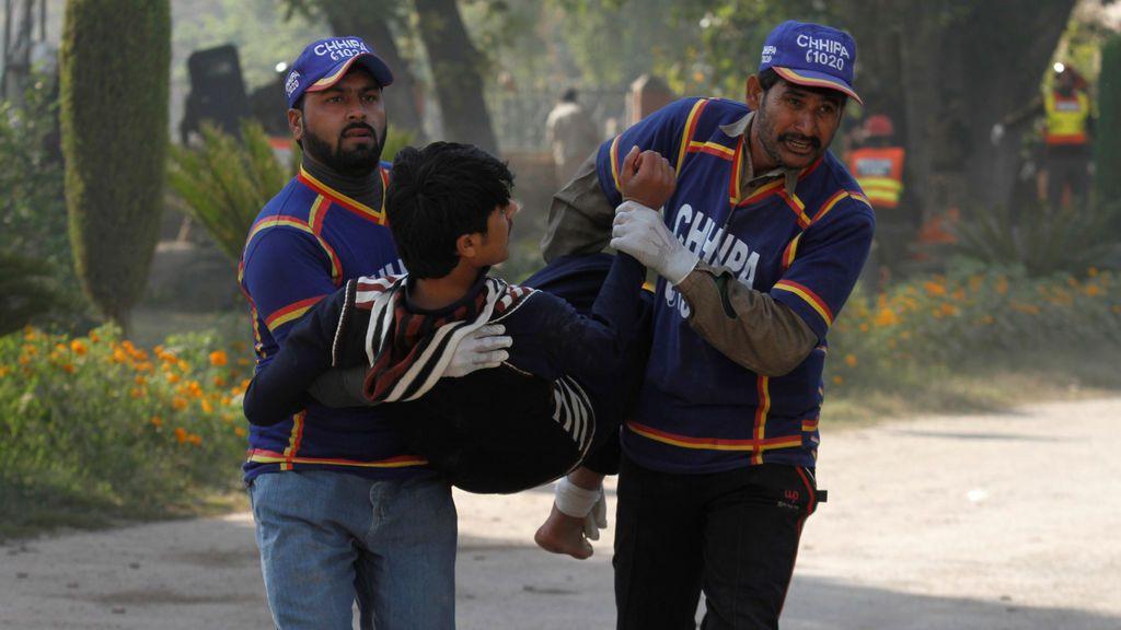 Los equipos de rescate ayudan a un estudiante lesionado en el tiroteo en la Dirección del Instituto de Agricultura en Peshawar, Pakistán