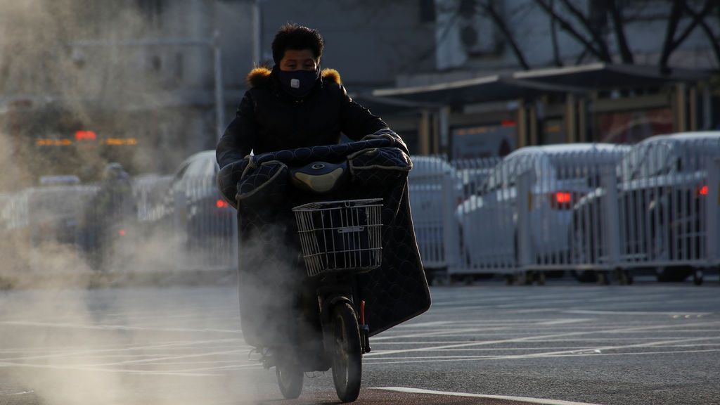 Un hombre monta un scooter eléctrico al lado de humeantes tapas de registro en un día frío en Beijing, China