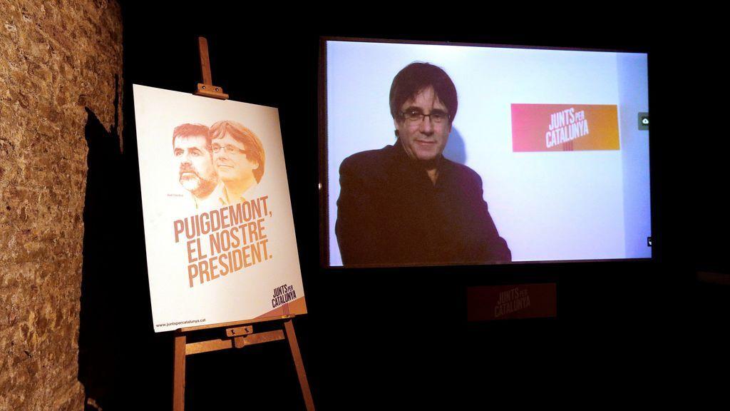 Carteles electorales de los candidatos de Junts per Catalunya durante la inauguración de la sede de campaña de la coalición electoral independentista catalana, en la que su cabeza de lista, Carles Puigdemont, huido de la justicia en Bélgica, se ha dirigido por videoconferencia a los asistentes al acto