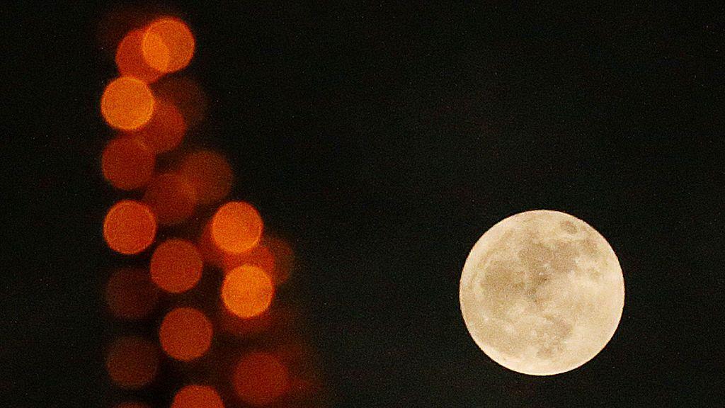 Una luna llena se representa detrás de las luces de neón en Nantong, provincia de Jiangsu, China