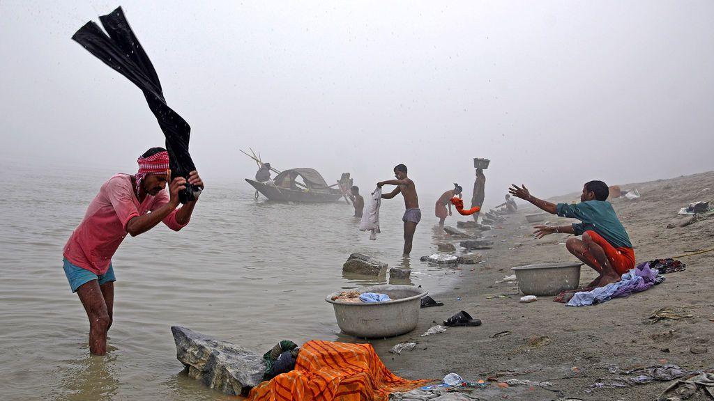 La gente lava ropa en las orillas del río Brahmaputra en una mañana de niebla de invierno en Guwahati, India